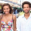 Young couple walking past restaurants in the summer - Stockfoto