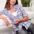 Woman with a remote control — Stock Photo