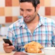 Stock Photo: Man eating croissant and texting