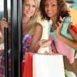 Portrait of two girls with shopping bags — Stock Photo
