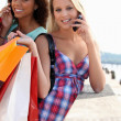 Two friends with shopping bags holding mobile phones — Stock Photo