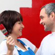 Stock Photo: Couple painting wall red