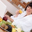 Woman using a laptop while eating a fruity breakfast - Stock Photo