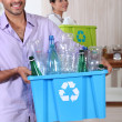 Couple recycling plastic bottles - Stockfoto
