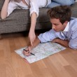 Foto Stock: Young couple looking at a map