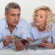 Middle-aged couple leafing through a brochure — Stock Photo #7949838