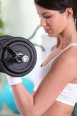 Young woman doing bicep curls in a gym — Stock Photo