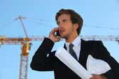 Businessman on a construction site talking on his cell phone — Stock Photo