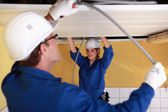 Two electricians working on the ceiling — Stock Photo