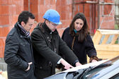 Architect reviewing a building plan with his clients — Stock Photo