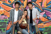 Three guitarists behind a tagged wall — Stock Photo