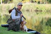 Un cazador y su perro junto a un río. — Foto de Stock