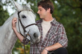 Man looking after horse — Stock Photo