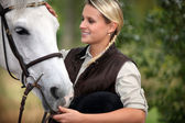 Young lady stroking her horse — Stockfoto