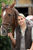Young blonde woman and a horse in front of a stable — Stock Photo