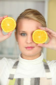 Woman holding orange halves to her face — Stock Photo