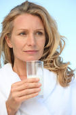 Woman outdoors in dressing gown holding glass of milk — Stock Photo