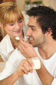 Man feeding his girlfriend yogurt — Stock Photo