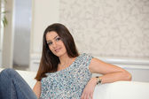 Brunette sat casually on sofa — Stock Photo