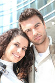 Couple stood outside high-rise building — Stockfoto