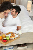 Clothed couple kissing in bed — Stock Photo