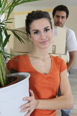 Couple carrying boxes and house plant — Stock Photo