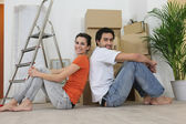 Couple sitting back to back next to step ladder — Stock Photo