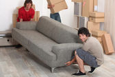 Picture of friends moving a couch — Stock Photo