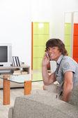 Junger mann bei einem aufruf in seinem wohnzimmer — Stockfoto