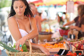 Sexy brunette buying vegetables at open air market — Stock Photo