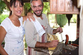 Couple cooking sausages on the barbecue — Stock Photo
