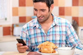 Man eating croissant and texting — Stock Photo