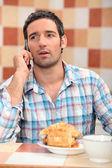 Man tar ett samtal på frukost — Stockfoto