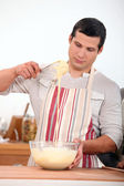 Young man wearing an apron and doing dough — Stock Photo
