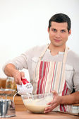 Young man using an electric egg beater — Stock Photo