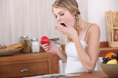 Young woman yawning over breakfast — Stock Photo