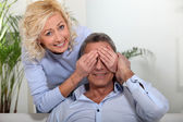 遮住她丈夫的眼睛与她的手的女人 — 图库照片
