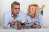 Middle-aged couple leafing through a brochure — Stock Photo