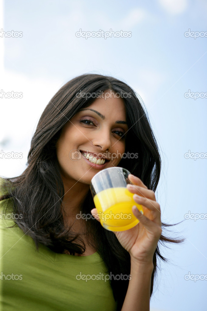 Woman drinking glass of orange juice outdoors  Stock Photo #7945719