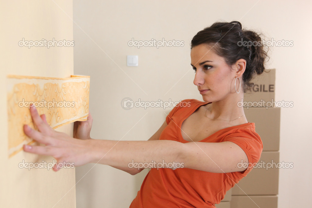 Young woman putting up wallpaper  Stock Photo #7947397