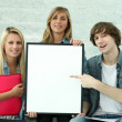 Three students holding a board left blank for your image - Stockfoto