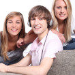 A boy listening music and two blonde girls behind a couch — Stock Photo