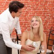 Man giving surprise gift to woman in restaurant — Stock Photo #7951749