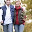 Foto Stock: Couple taking walk through woodland