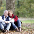 Couple sat by tree — Stock Photo