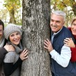Adult family around a tree — Stock Photo