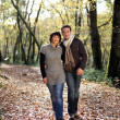 Couple walking through park in autumn — Stock Photo