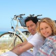 Couple on holiday sitting in front of bicycles — Stock Photo