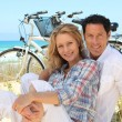 Stock Photo: Couple on the beach with bikes