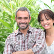 Couple stood surrounded by plants — Stock Photo #7952610